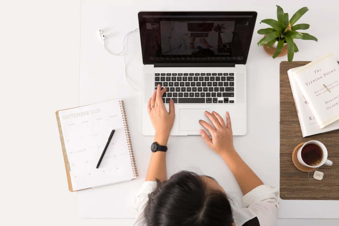 Woman sitting at a laptop doing seo research for a blog post