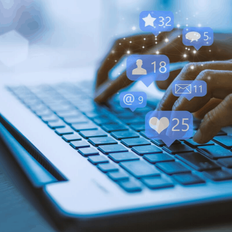 Blue toned image of someone typing on a laptop with graphic overlay of social media buttons