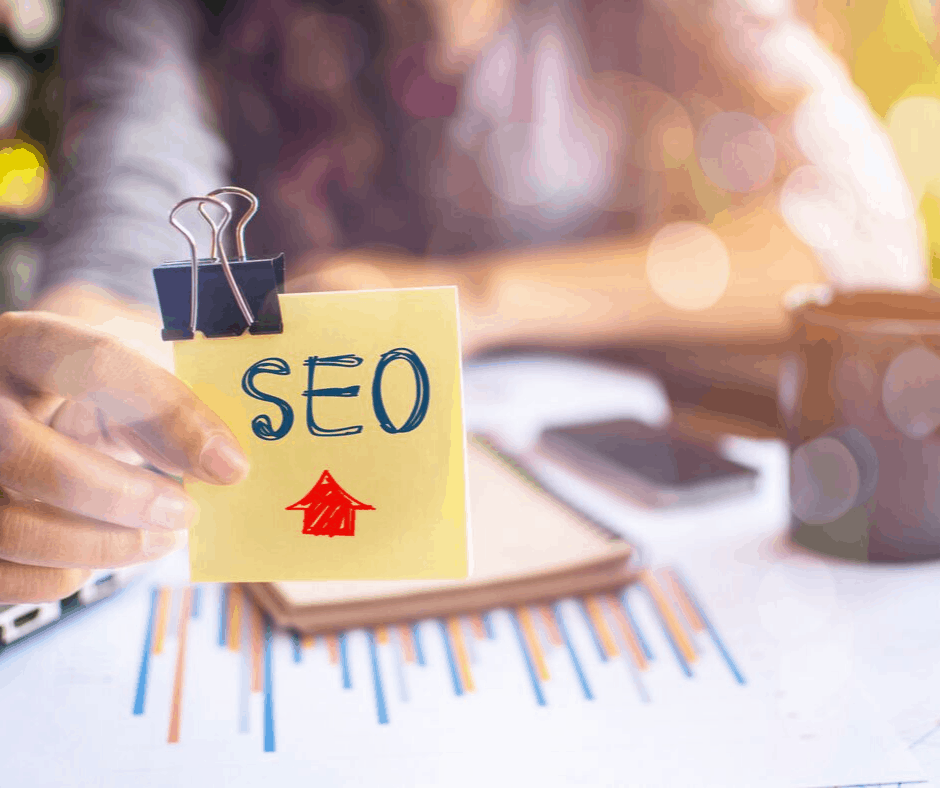 The word SEO on a yellow post it note being held up by a woman at a desk with a coffee cup
