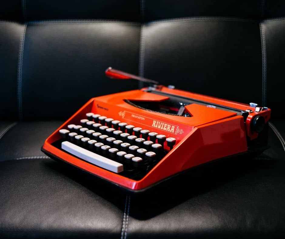 Red typewriter on black leather coach